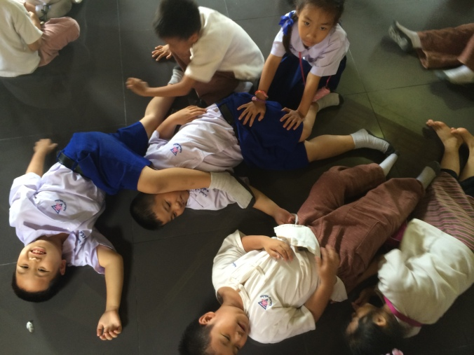 Elementary ESL students lay on the ground in Chiang Mai, Thailand