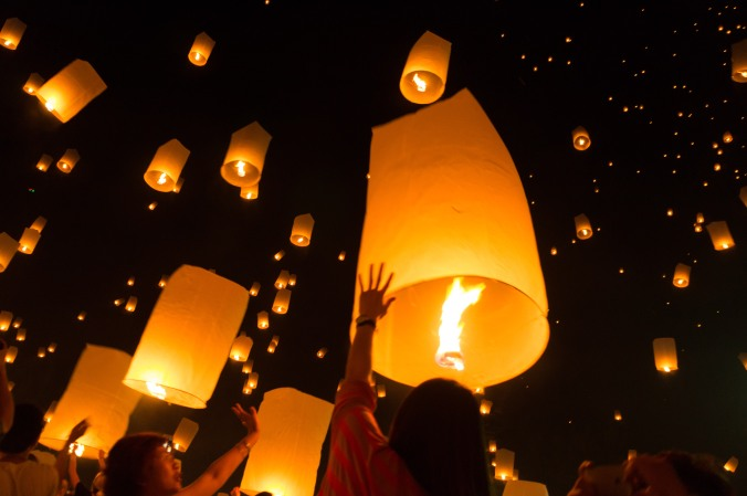 Women release a lantern into the night sky at Chiang Mai, Thailands Yi Peng lantern festival