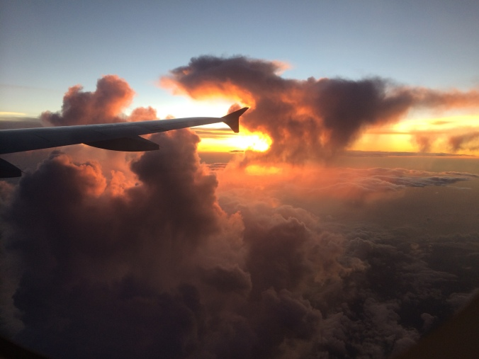 A plane wing with clouds and a sunset out an airplane window