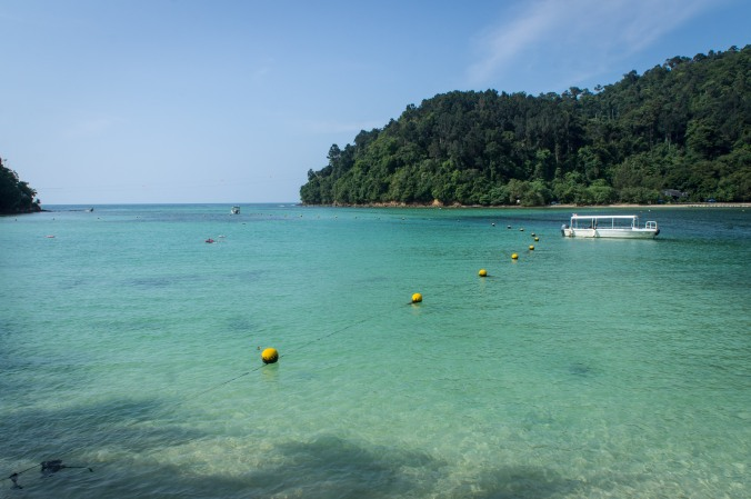 View of the water, a boat, and Gaya Island from the shore of Sapi Island, Malaysia