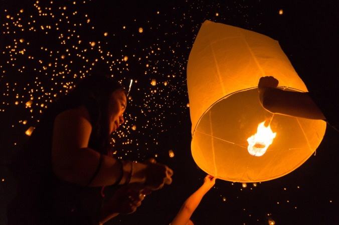 Women release one large lantern at Chiang Mai, Thailand's Loy Krathong/Loi Krathong lantern release festival