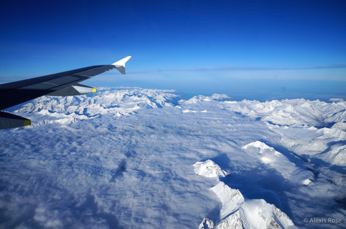 Airplane wing flies above clouds and mountains somewhere in the Alps