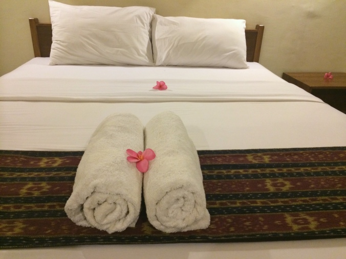 Medana Bay Marina bed with towels and flowers in Lombok, Indonesia