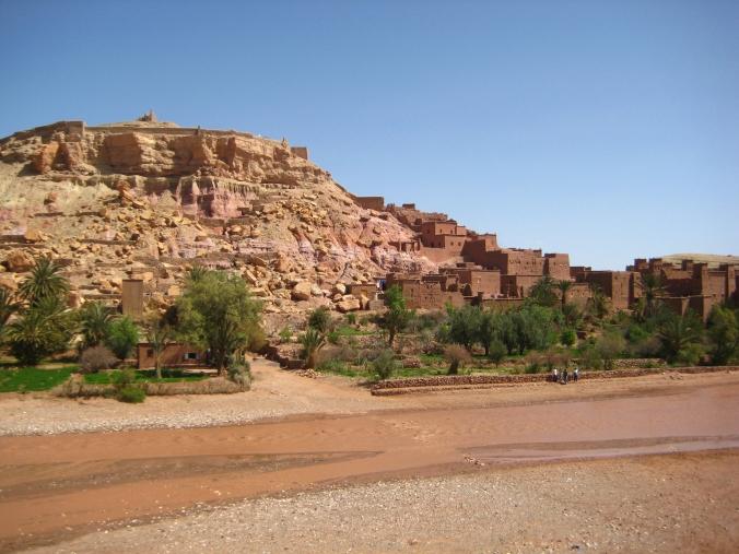 A brown stream runs in front of the earthen city of Aït Ben Haddou, Morocco