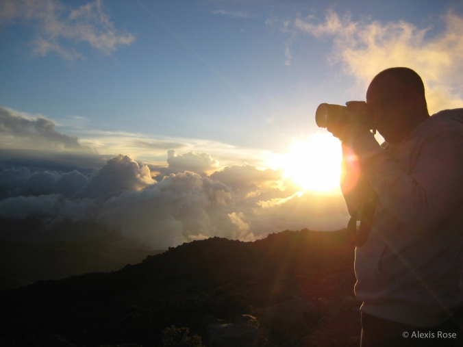 Man takes a photo at sunset on Mauna Kea in Hawaii