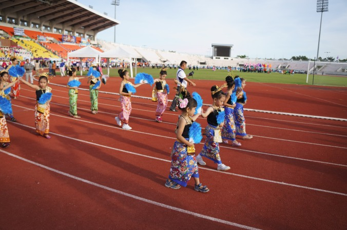 Children dressed in costumes walk on a running track at a Sports Day activity in Chiang Mai, Thailand