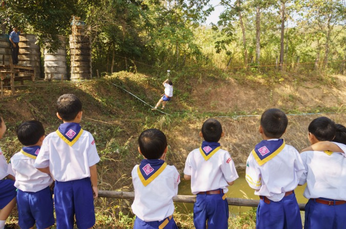 Boy scouts watch their friend ride a zip line