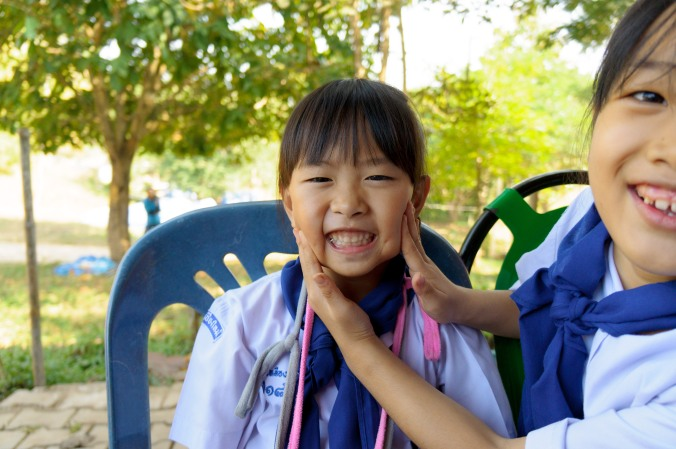 Girl scout has her cheeks squished into a smile in Chiang Mai, Thailand