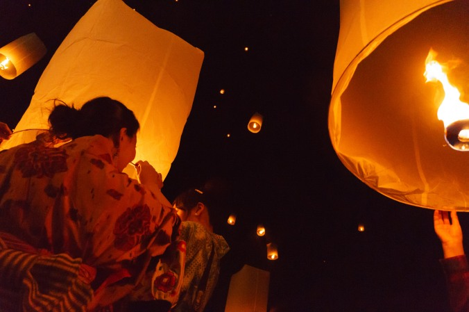 A Japanese woman wears a kimono and lights a sky lantern during a New Year's Eve 2014 celebration in Chiang Mai, Thailand