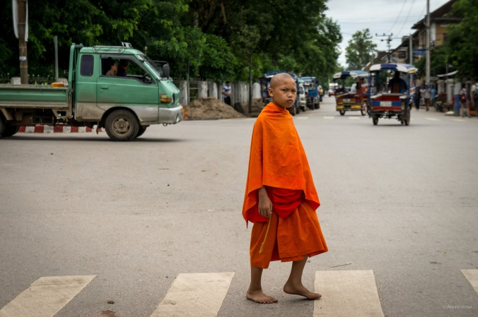 A child monk walks across the street in Luang Prabang, Laos